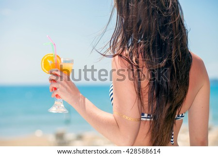 Happy woman with cocktail on the beach during tropical vacation - stock photo