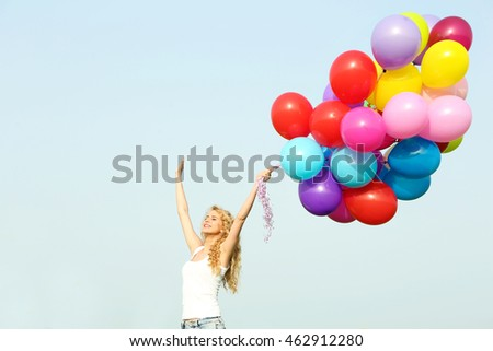 Happy woman with colorful balloons on blue sky background