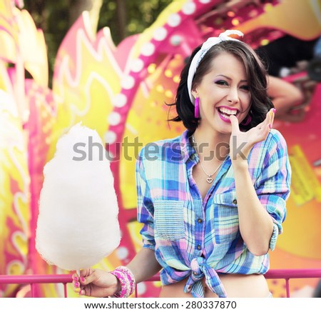 Happy Woman with Cotton Candy in Amusement Park Smiling