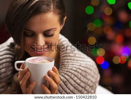 Happy woman with cup of hot chocolate with marshmallow in front of christmas lights
