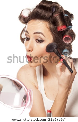 happy woman with curlers and bad makeup applied blush - stock photo