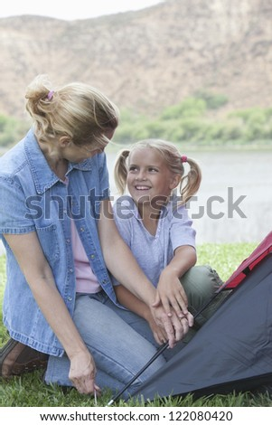 Happy woman with cute daughter fixing tent on vacations