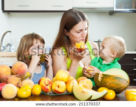Happy woman with daughters together with melon and peaches over dining table at home interior