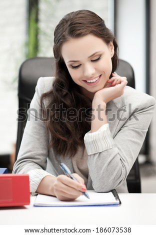 happy woman with documents writing something down - stock photo
