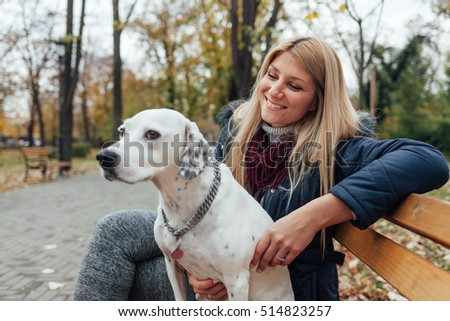 Happy woman with dog sitting on the wooden bench in the park