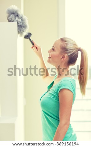 happy woman with duster cleaning at home - stock photo