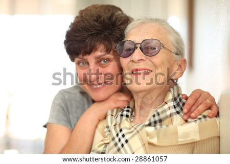 Happy woman with elderly mother, laughing together. Shallow DOF, focus on the senior woman. - stock photo