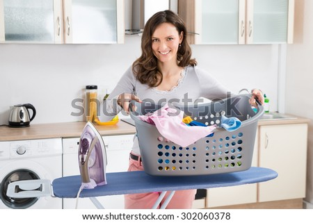 Happy Woman With Electric Iron And Basket With Clothes On Ironing Board