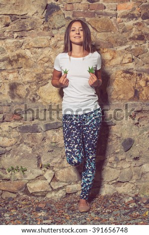 Happy woman with fresh leaves of cannabis plant in her hands standing outside in a sunny day - stock photo