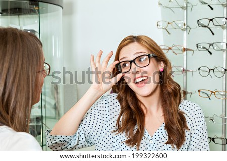 Happy Woman With Friend Examining Eyeglasses In Optician Store - stock photo