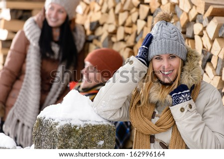 Happy woman with friends smiling outside winter countryside cottage - stock photo