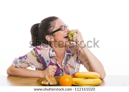 Happy woman with fruits and cakes on table eating big apple. - stock photo