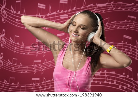happy woman with headphone listening music and smiling, wearing pink singlet  - stock photo