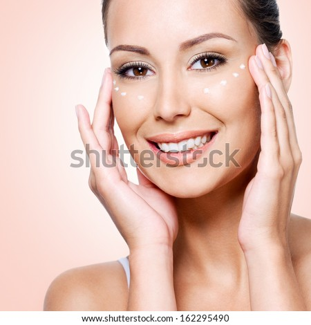 Happy woman with healthy face applying cosmetic cream under the eyes