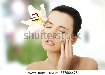 Happy woman with healthy skin and lily flower
