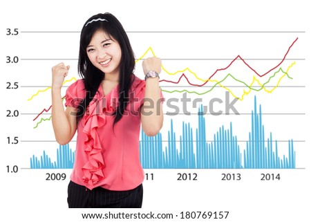 Happy woman with her arms raised up in front of profit chart