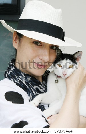 Happy woman with her black and white cat.