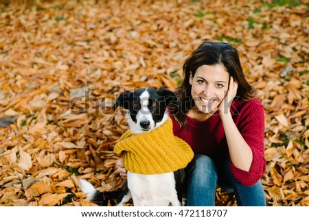 Happy woman with her dog enjoying autumn season together. Funny cute pet wearing warm scarf.