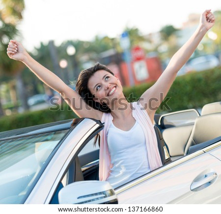 Happy woman with her new car and arms up - stock photo