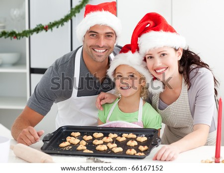 Happy woman with husband and daughter ith their biscuits ready to eat in the kitchen - stock photo