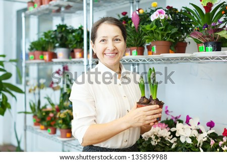 Happy  woman with hyacinth (Hyacinthus) in flower store - stock photo