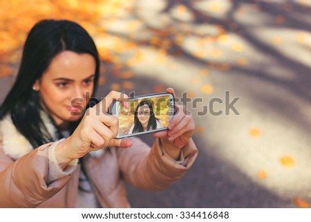 Happy woman with jacket taking selfie with smartphone in nature. Vintage effect. - stock photo