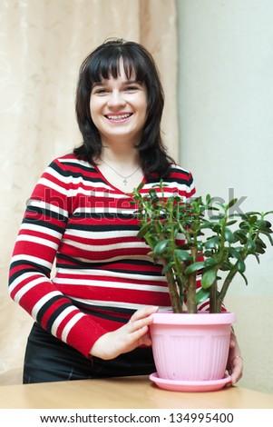 Happy woman with  jade in flowering pot in  room - stock photo