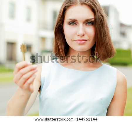 happy woman with keys standing near house