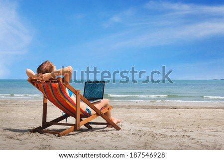 happy woman with laptop on the beach - stock photo