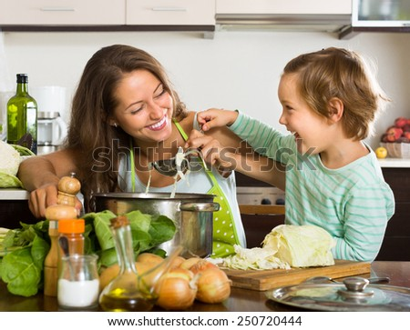 Happy woman with little daughter cooking with vegetables at home kitchen  - stock photo