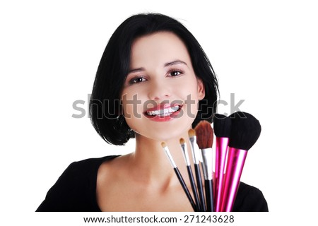 Happy woman with make up brushes. - stock photo