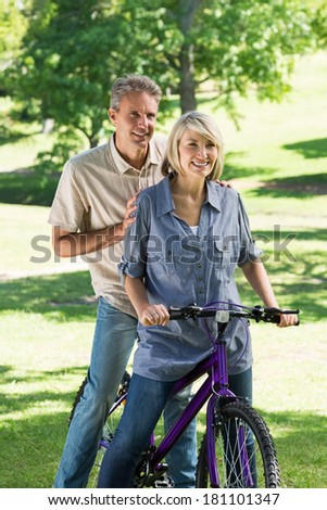 Happy woman with man riding bicycle in park
