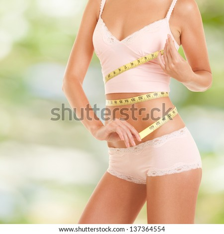 Happy woman with measure tape - stock photo