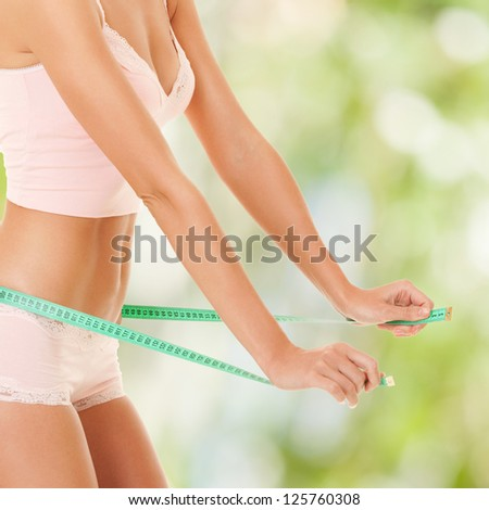 happy woman with measure tape on nature background - stock photo