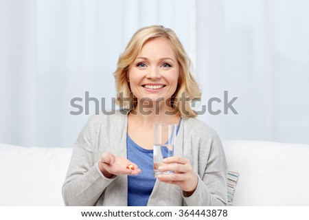 happy woman with medicine and water glass at home - stock photo