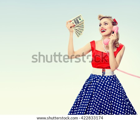 Happy woman with money, talking on phone, dressed in pin-up style dress in polka dot, with blank copyspace area for text or slogan. Model posing in retro fashion and vintage concept studio shoot. - stock photo
