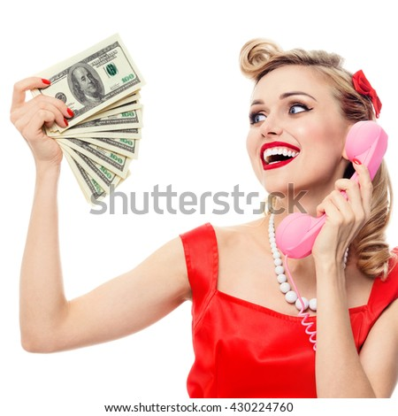 Happy woman with money, talking on phone, dressed in pin-up style dress, isolated over white. Caucasian blond model posing in retro fashion and vintage concept studio shoot. - stock photo
