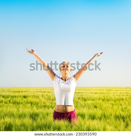 Happy woman with outstretched arms in a wheat field