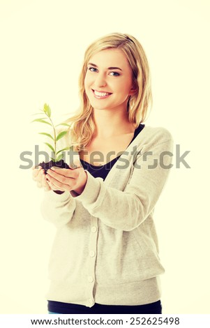 Happy woman with plant and dirt in hand - stock photo