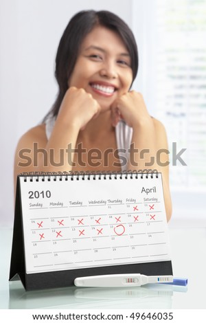 Happy woman with positive pregnancy test and calendar. A concept being success to get pregnant