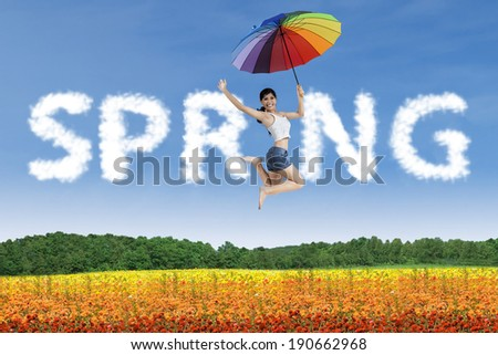 Happy woman with rainbow umbrella jumping in a colorful garden - stock photo