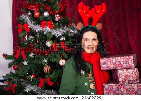 Happy woman with reindeer ears holding Christmas gifts in front of decorated tree - stock photo