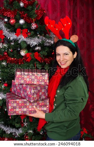 Happy woman with reindeer ears holding Christmas presents and standing near xmas tree in her house - stock photo