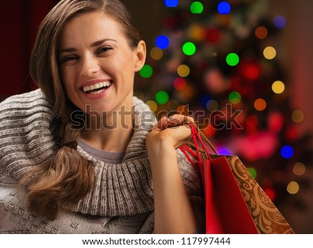 Happy woman with shopping bag in front of Christmas lights - stock photo