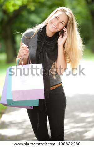Happy woman with shopping bags calling by cellphone - stock photo