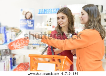 Happy woman with shopping basket choosing products in supermarket - stock photo