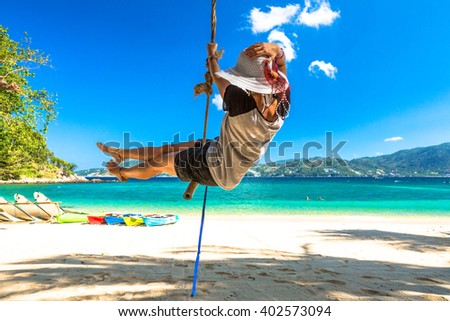 Happy woman with shorts, shirt and wide-brimmed hat swinging in Paradise Beach, the most famous beach in Patong, Phuket, Thailand. On background blue tropical sea, kayaking and white sand. - stock photo