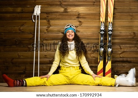Happy woman with skis and ski boots sitting on a floor near wooden wall - stock photo
