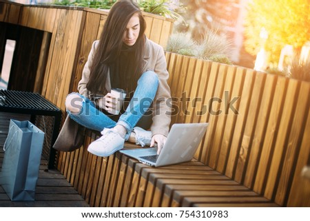 Happy woman with smartphone or laptop in city centre on wooden place
