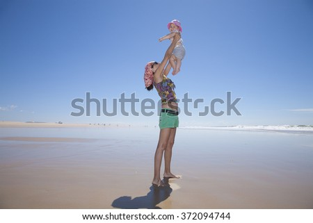 happy woman with sunglasses green shorts headscarf and baby pink hat in arms at beach Conil Cadiz Spain - stock photo